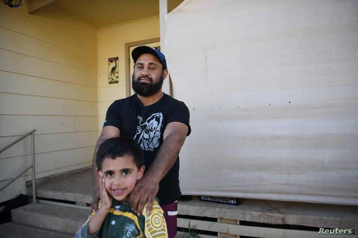 A Barkindji man, hunter and goat musterer Kyle Philip poses for a photograph with his son Kaleb Philip at their home in…
