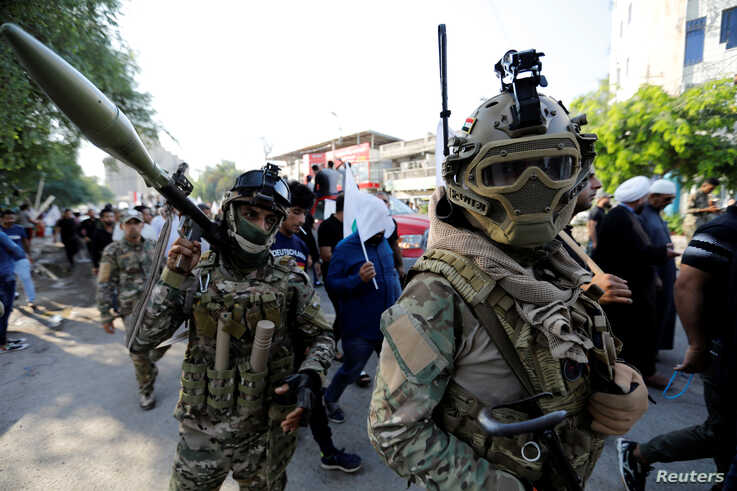 Iraqi Popular Mobilisation Forces (Hashid Shaabi) are seen at a march during the funeral of members of Shi'ite group Asaib Ahl…