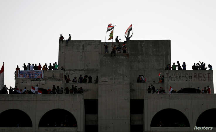 Demonstrators are seen on a building during a protest over corruption, lack of jobs, and poor services, in Baghdad, Iraq…