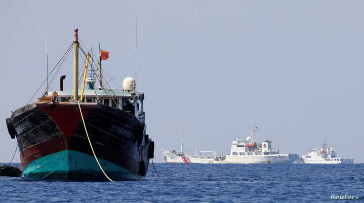 China Coast Guard vessels patrol past a Chinese fishing vessel at the disputed Scarborough Shoal, April 5, 2017. Picture taken…