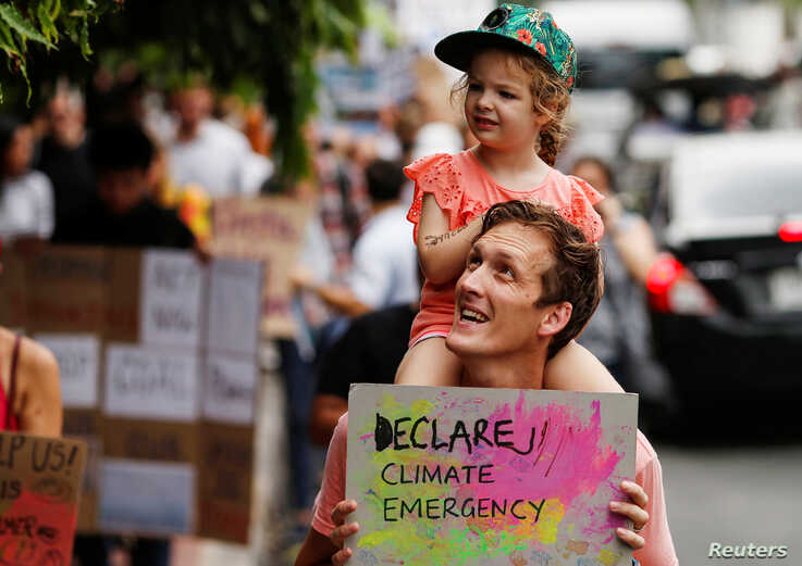 An environmental activist carries his daughter on his shoulders as they participate in a Global Climate Strike near the…