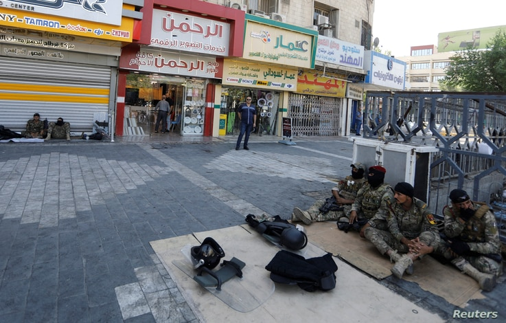Iraqi security forces rest in Tahrir square after the lifting of the curfew, following four days of nationwide anti-government…