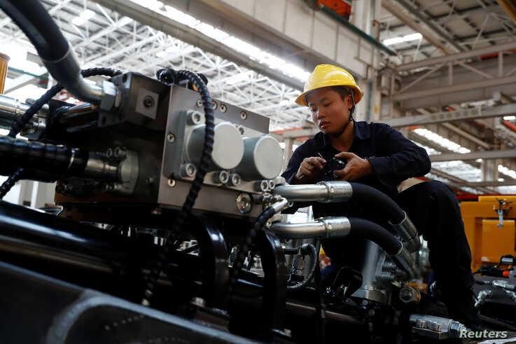 An employee works at a manufacturing plant of Sany Heavy Industry Co. during a government-organised tour of manufacturers based…