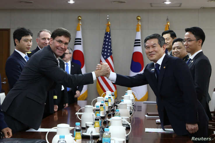U.S. Defense Secretary Mark Esper clasps hands with South Korean Defense Minister Jeong Kyeong-doo during their meeting in…