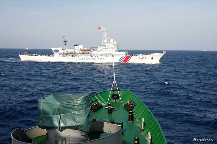 FILE PHOTO: A ship (top) of the Chinese Coast Guard is seen near a ship of the Vietnam Marine Guard in the South China Sea,…
