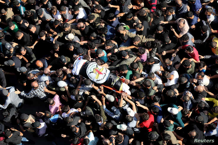 Mourners carry the body of Palestinian Islamic Jihad field commander Baha Abu Al-Atta during his funeral in Gaza City November…