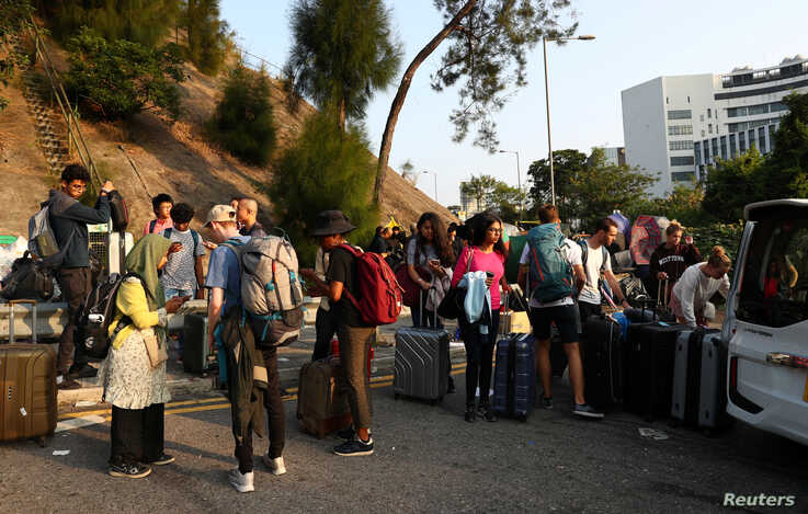 International students of the Chinese University of Hong Kong evacuate with their suitcases after anti-government protesters…