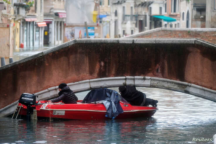 A boat tries to pass under a bridge during a period of seasonal high water in Venice, Italy, November 15, 2019. REUTERS/Manuel…
