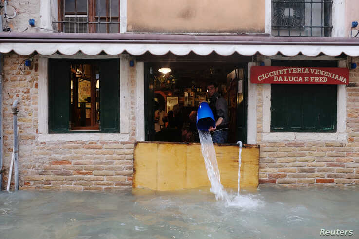 A man removes water from the flooded shop during a period of seasonal high water in Venice, Italy November 15, 2019. REUTERS…