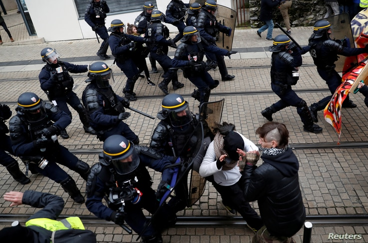 """Protesters clash with French riot police during a demonstration to mark the first anniversary of the """"yellow vests"""" movement in…"""