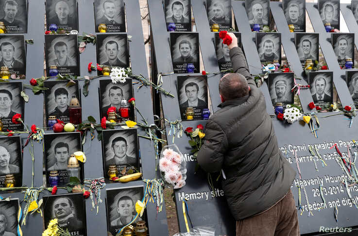"""A man places flowers as he takes part in a commemoration ceremony at a monument to the so-called """"Heavenly Hundred"""", the anti…"""