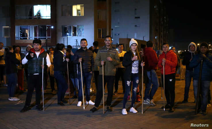 Residents hold sticks as they stand in front of their apartment block to guard their homes from possible looting after a curfew…