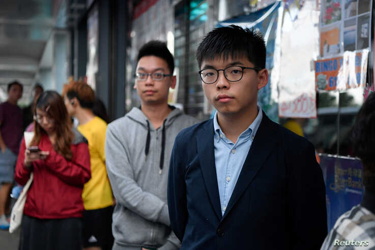 Disqualified candidate and pro-democracy activist Joshua Wong stands in line to vote in the district council elections in Hong…
