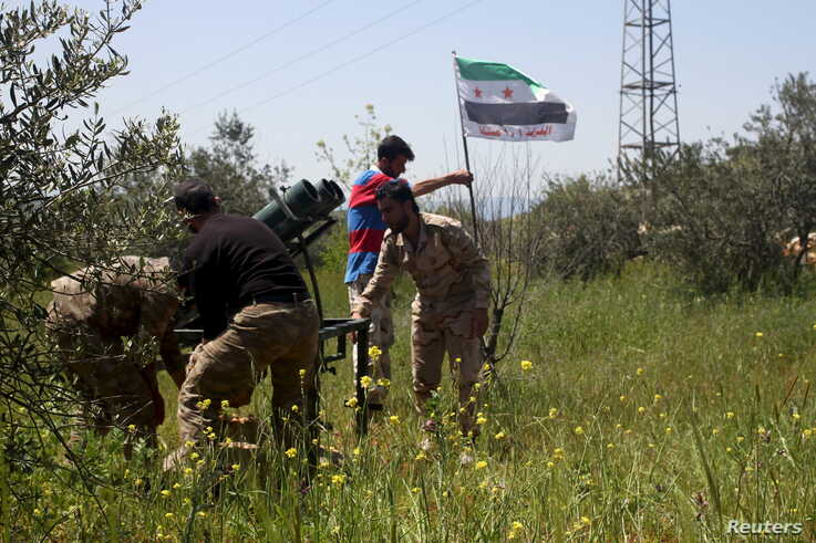 Free Syrian Army fighters prepare a Katyusha rocket launcher before firing towards forces loyal to Syria's president Bashar Al…