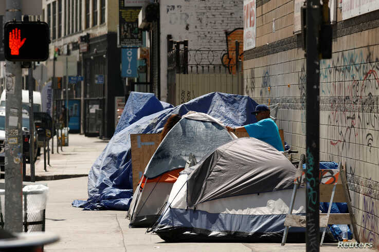 Tents and tarps erected by homeless people are shown along sidewalks and streets in the skid row area of downtown Los Angeles,…