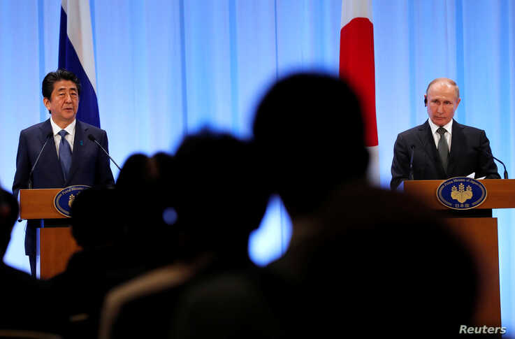 Russian President Vladimir Putin (R) and Japanese Prime Minister Shinzo Abe attend a news conference at G20 leaders summit in…