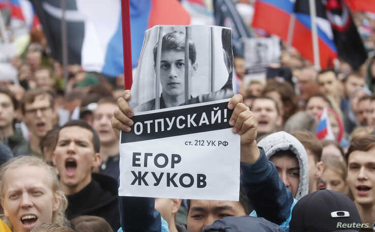 A supporter of student and blogger Yegor Zhukov, who was detained during a recent protest for fair elections, holds a placard…
