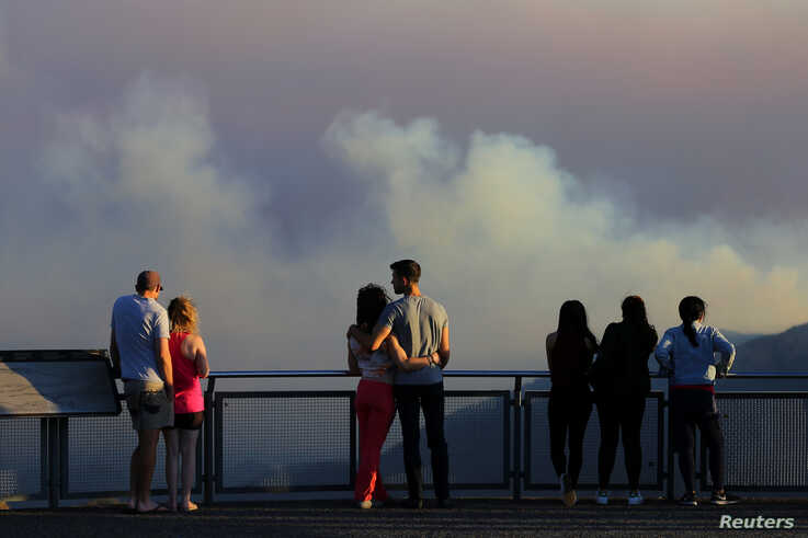 People watch as smoke from the Green Wattle Creek fire is seen from Echo Point lookout in Katoomba, as bushfires continue to…