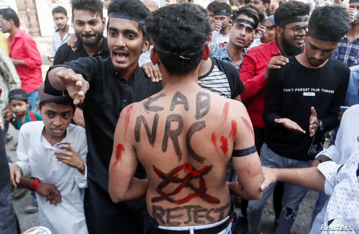 A man with a slogan painted on his back is seen during a protest against a new citizenship law, on the outskirts of Mumbai,…