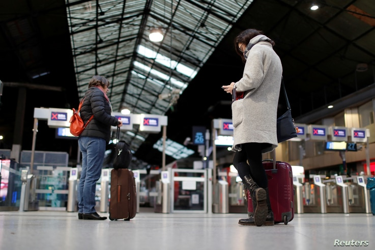 Travelers wait for a train at the Saint-Lazare railway station during a strike by all unions of French SNCF workers and the…