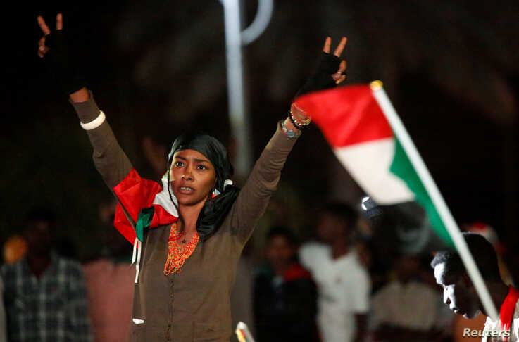 A woman flashes the victory sign during the first anniversary of the start of the uprising that toppled long-time ruler Omar al…