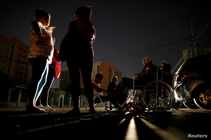Patients with kidney disease and their relatives wait on the street for the return of electricity, in front of a dialysis…