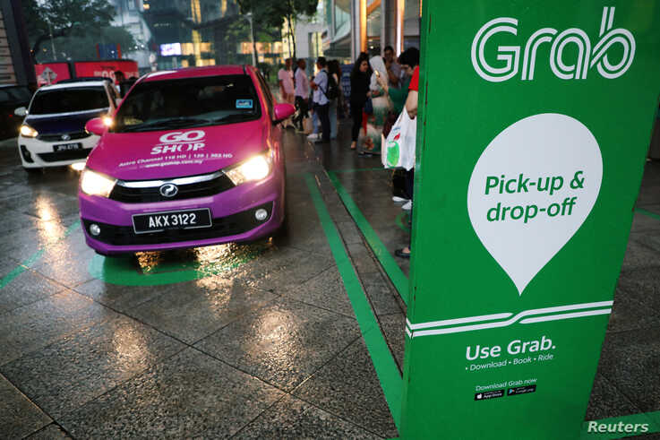A Grab pick-up and drop-off station is seen at the entrance of Kuala Lumpur City Centre in Kuala Lumpur, Malaysia October 3,…