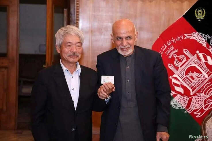 Afghanistan's President Ashraf Ghani (R) and Japanese doctor Tetsu Nakamura pose for a photo, in this undated picture, in Kabul…