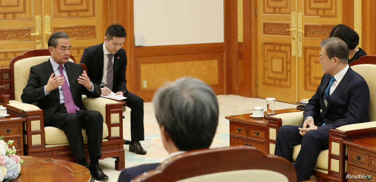 Chinese Foreign Minister Wang Yi talks with South Korean President Moon Jae-in during their meeting at the Presidential Blue…