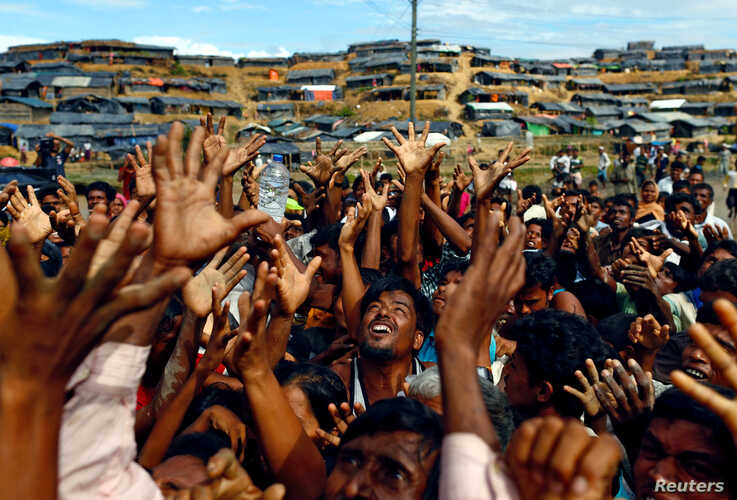 FILE PHOTO: Rohingya refugees stretch their hands to receive aid distributed by local organisations at Balukhali makeshift…