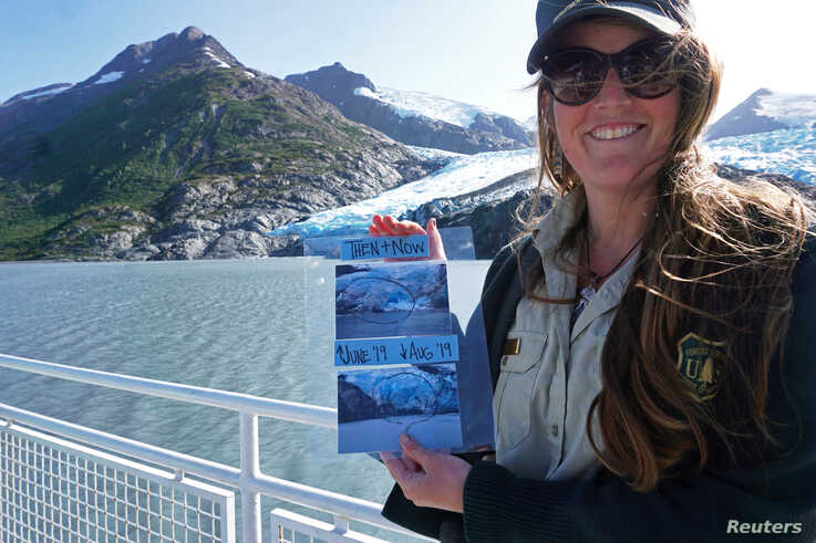 Chugach National Forest ranger Megan Parsley holds photos showing this summer's ice loss at the face of Portage Glacier, Alaska…