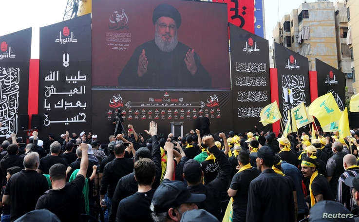 Lebanon's Hezbollah leader Sayyed Hassan Nasrallah gestures as he addresses his supporters via a screen during the religious…