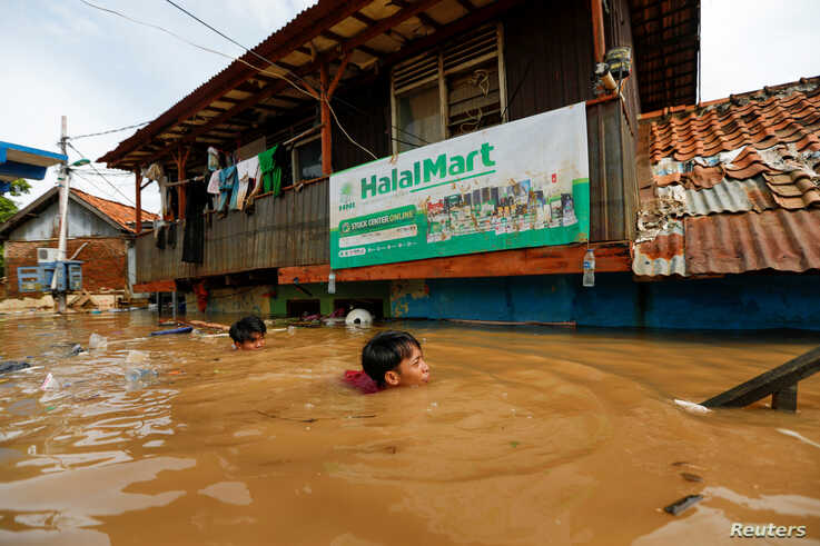 Men swim as they collect items from their houses, flooded after heavy rains in Jakarta, Indonesia, January 2, 2020. REUTERS…