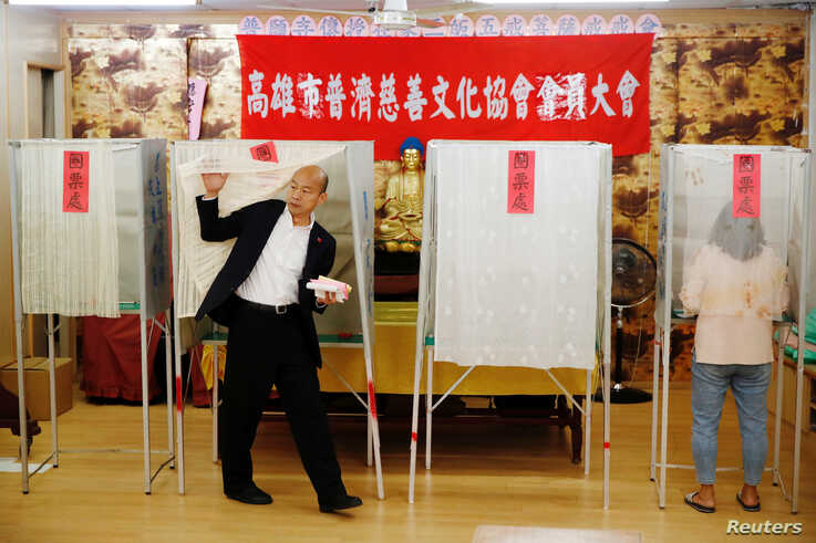 Taiwan's opposition Kuomintang Party (KMT) presidential candidate Han Kuo-yu votes at a polling station during general…