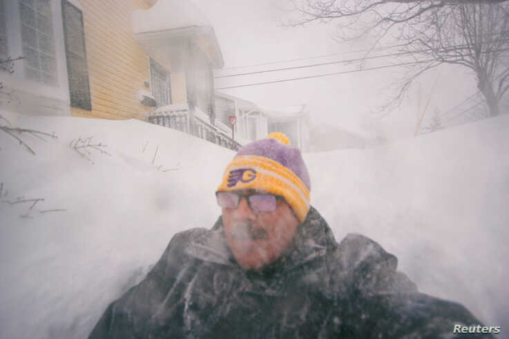 A man is pictured in a snowy street in St. John's, Newfoundland and Labrador, Canada January 17, 2020. Zach Bonnell/via REUTERS…