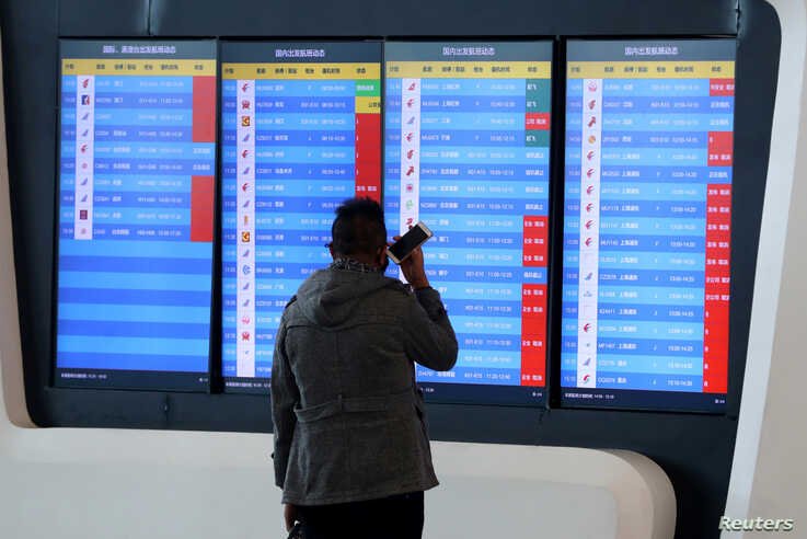 A man stands in front of a screen showing that multiple departure flights have been cancelled after the city was locked down…