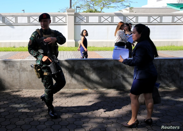 Philippine security personnel patrol near U.S Visa applicants after an Improvised Explosive Device (IED)  was found near the US…