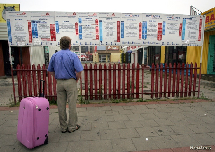 Andrzej looks at the timetable at an international bus station in Bialystok, eastern Poland, August 8, 2006, before his wife…