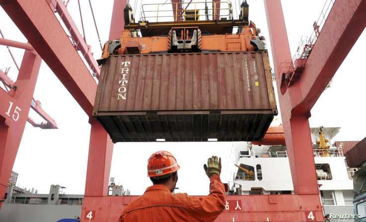 An employee guides as a crane unloads shipping containers from a cargo ship at a port in Lianyungang, Jiangsu province March 8,…