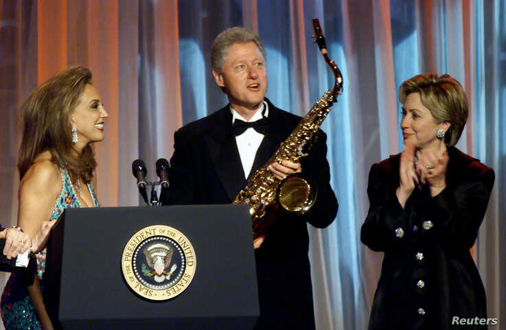 Denise Rich (L) presents former U.S. President Bill Clinton with a saxaphone at the G&P Foundation gala in New York City, in…