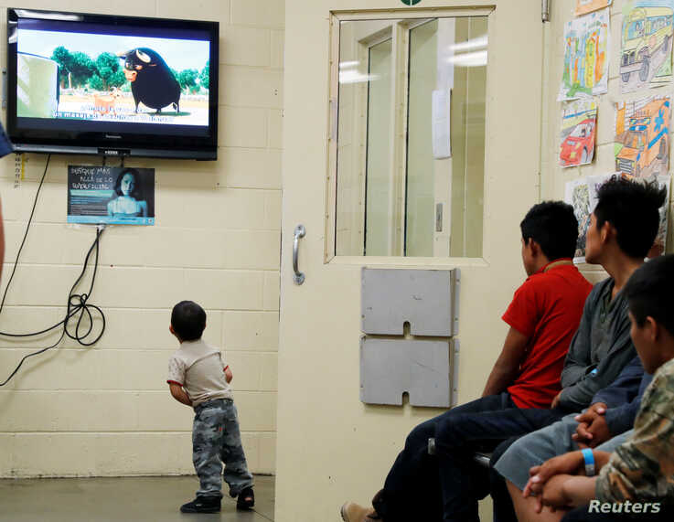 A detained immigrant child watches a cartoon while awaiting the arrival of U.S. first lady Melania Trump with other young…