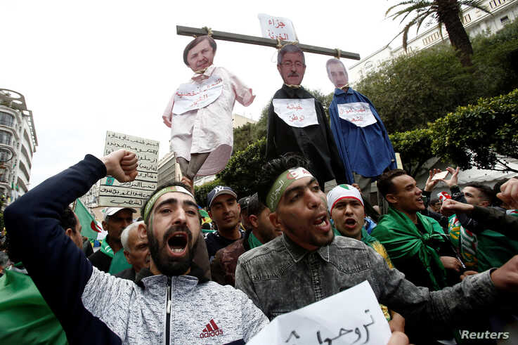 People gesture and carry a mock hangman with the faces of Algerian businessman Ali Haddad, former prime minister Ahmed Ouyahia,…