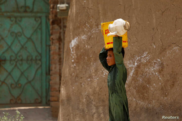 A boy from an Afghan refugee family, carries a bucket of water on his head, filled at a nearby tap, on the outskirts of…