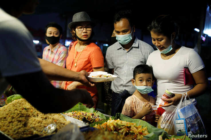 A family wearing protective masks purchases food at a market in Yangon, Myanmar, February 3, 2020. REUTERS/Ann Wang