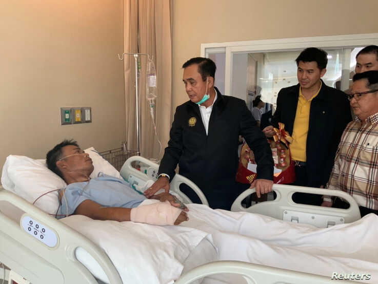 Thailand's Prime Minister Prayuth Chan-ocha visits an injured man in a hospital following a gun battle involving a Thai soldier…