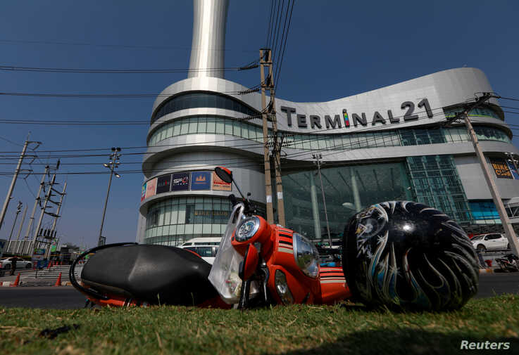 A motorcycle and helmet that belongs to a victim lie in front of the Terminal 21 shopping mall following a gun battle involving…