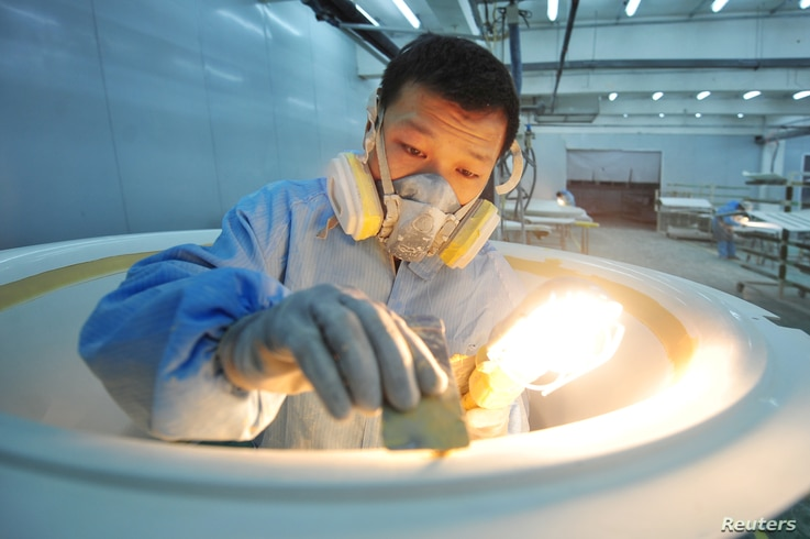 A worker wearing a mask polishes parts for computed tomography (CT) scanners at a factory in Qingdao, Shandong province, China, Feb. 9, 2020. (Credit: China Daily)