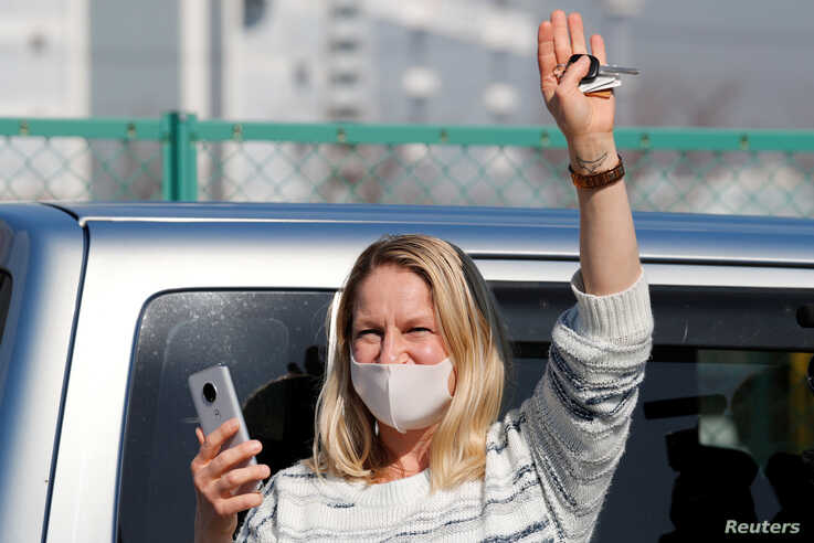 A woman waves from outside Daikoku Pier Cruise Terminal as she communicates via phone with a passenger (not pictured) standing…