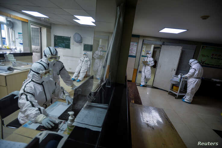 Medical workers in protective suits work inside an isolated section at a community health service center, which has received…