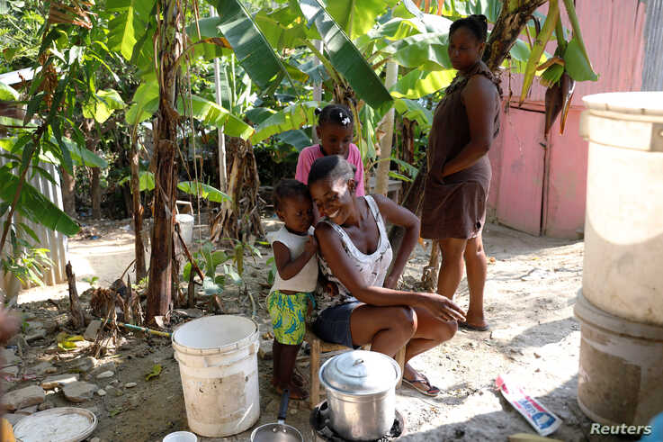 Frena Remorin, 30, (seated) cooks bananas in the improvised kitchen in the yard of her house in Jean-Rabel, Haiti January 31,…